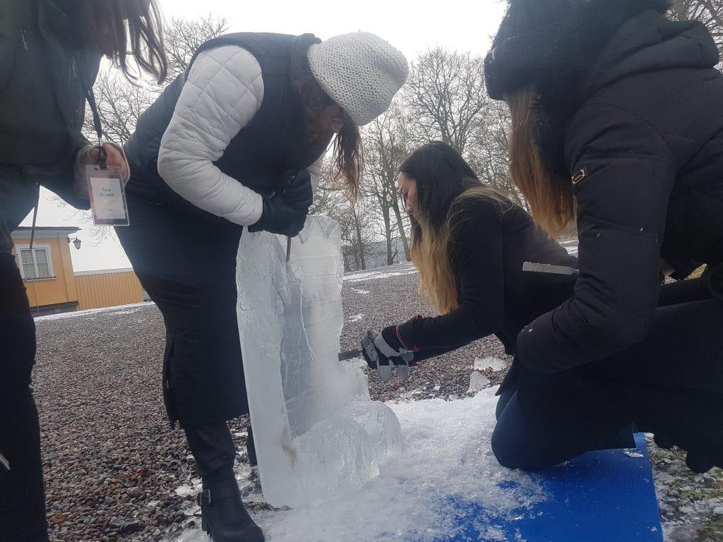 Aktivitet med isskulpturer där grupp sågar is med motorsåg